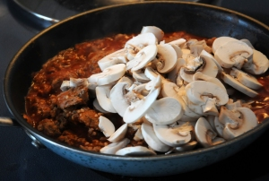 Add tomato sauce and mushrooms.